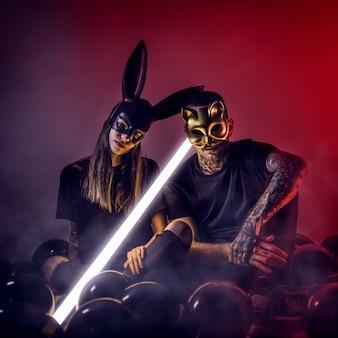 車とウサギのマスクとライトランプと黒い風船と一緒に座っている若者