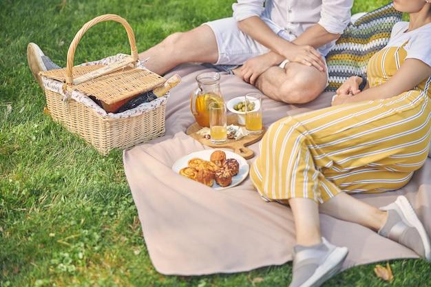 맛있는 식사와 차가운 음료와 함께 정원에서 함께 시간을 보내는 젊은 사람들