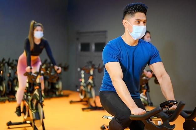 코로나 바이러스 발생 동안 얼굴 보호 마스크가있는 피트니스 체육관에서 젊은 사람들이 회전합니다.