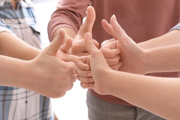 Молодые люди, стоящие в круге и показывающие жест вверх большим пальцем, как символ единства