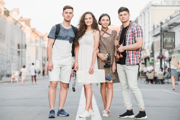 Young people standing on street with map and camera