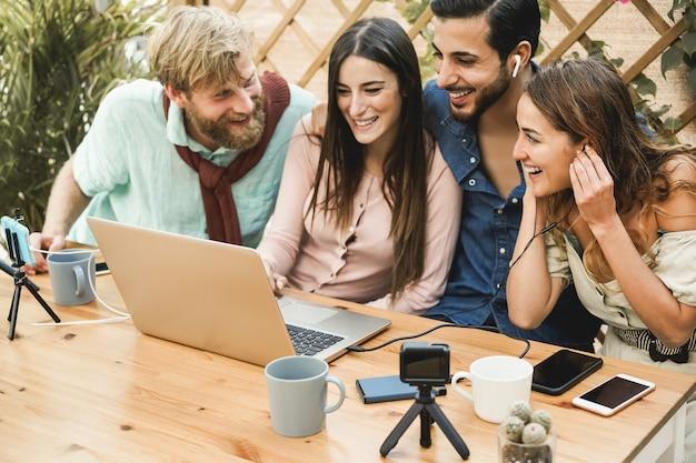 Молодые люди смотрят онлайн-трансляцию с помощью портативного компьютера и камеры мобильного телефона на открытом воздухе в ресторане