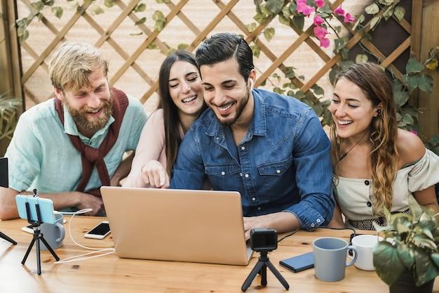 Молодые люди смотрят онлайн-трансляцию с помощью портативного компьютера и камеры мобильного телефона на открытом воздухе в ресторане Premium Фотографии