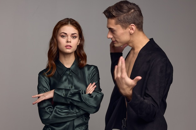 Young people in suits on a gray background gesturing with hands problems in the family conflict situation.