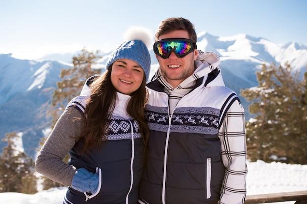 Молодые люди отдыхают после катания на лыжах в горах, зимнее время.