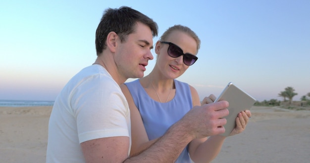 Молодые люди фотографируют закат на берегу