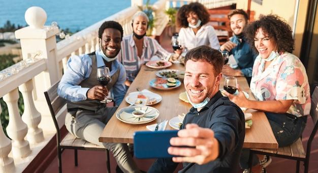 屋外のホームパティオで夕食を楽しみながら自分撮りをしている若者