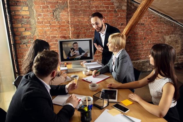 オフィスや居間で同僚とビデオ会議中に働いて話している若者