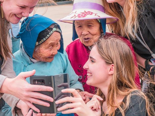 Молодые люди учат пожилых женщин пользоваться смартфоном