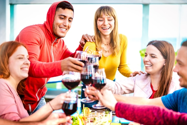 Young people toasting red wine at dinner party on multicolored clothes
