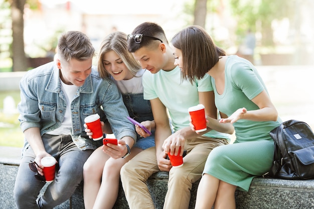 Young people typing at the smartphone. group of friends watching at their cell phones. youth and digital technology.