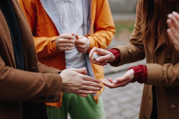 通りに立っている間消毒剤を使用している若者。手と消毒剤のクローズアップ。感染症からの保護の概念。