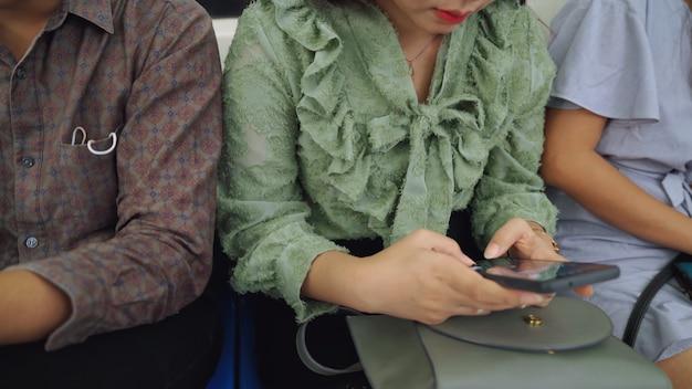 公共の地下鉄で携帯電話を使う若者たち。都市のライフスタイルとアジアでの通勤のコンセプト。