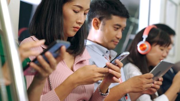 公共の地下鉄で携帯電話を使う若者