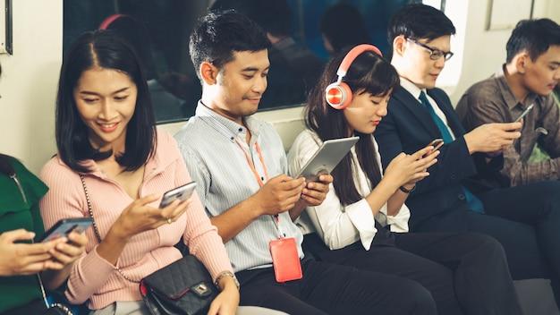 Молодые люди используют мобильный телефон в общественном метро