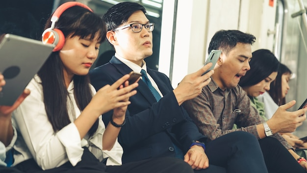 Young people using mobile phone in public underground train. urban city lifestyle and commuting in asia concept .