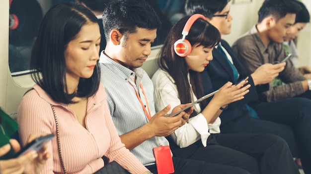 Young people using mobile phone in public underground train