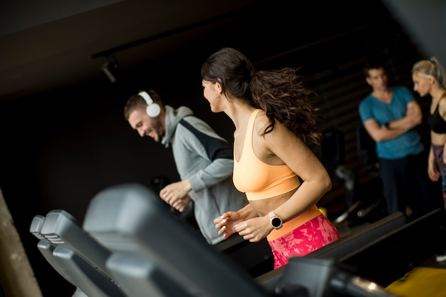 Young people using threadmill in modern gym