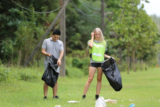 Young people volunteers collecting plastic bottles to trash bags in forest background.