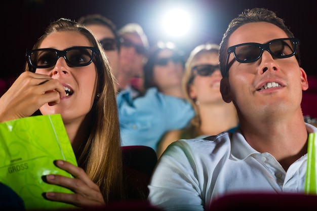 Young people watching 3d movie at movie theater