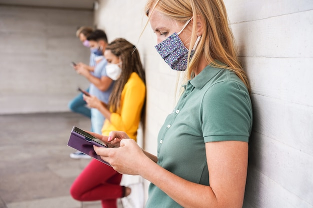 Young people wearing face safety masks using mobile phones while keeping social distance during coronavirus outbreak - technology and covid-19 spread prevention concept - focus on right woman eye