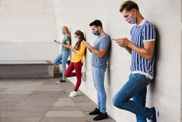 Young people wearing face safety masks using smart mobile phones while keeping social distance on coronavirus outbreak
