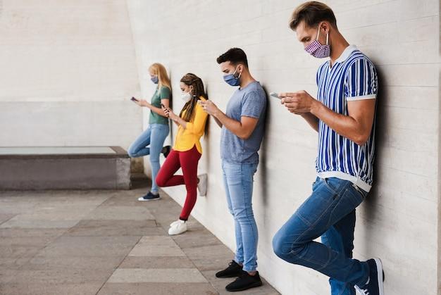 コロナウイルスの発生で社会的距離を保ちながら、スマート携帯電話を使用して顔の安全マスクを身に着けている若者