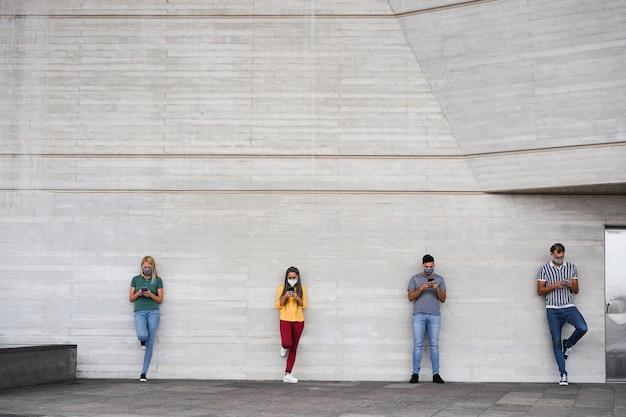 コロナウイルスの時間に社会的距離を保ちながら、スマート携帯電話を使用して顔の安全マスクを身に着けている若者