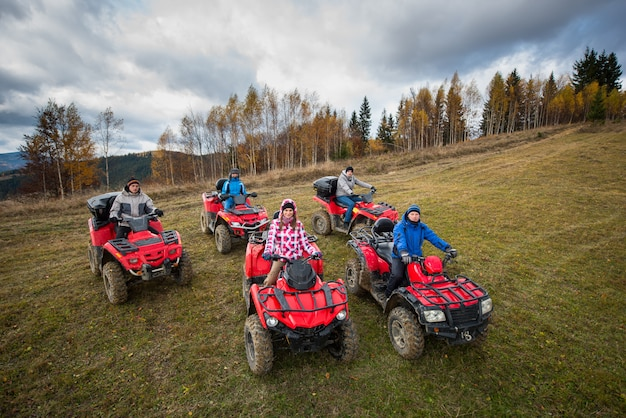 Young people in winter clothes on five red quad bikes on a countryside trail in nature under the sky with clouds