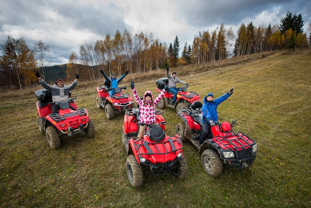 Young people in winter clothes with raised hands up on red atv off-road vehicles on a countryside trail in nature under the sky with clouds