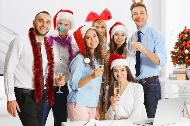 Молодые люди с бокалами шампанского празднуют рождество на корпоративной вечеринке в офисе