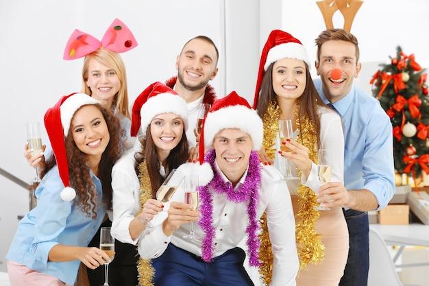 オフィスの企業パーティーでクリスマスを祝うシャンパンのグラスを持つ若者