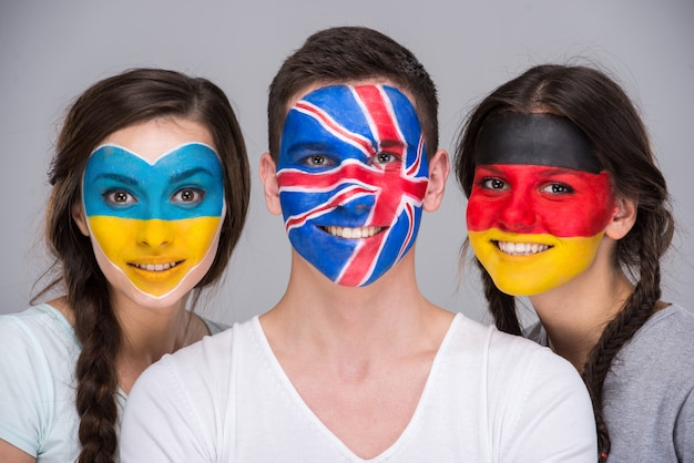 Young people with national flags painted on the faces.