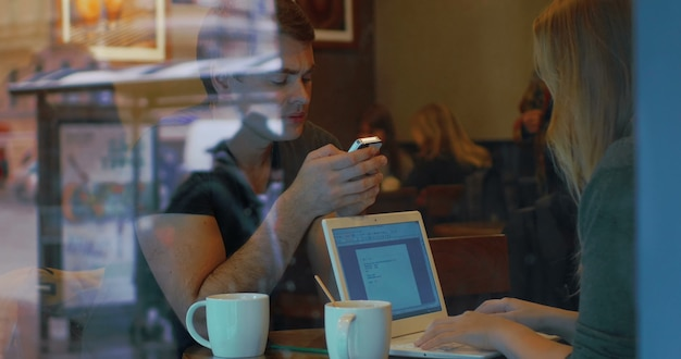 Young people with smart phone and laptop in cafe