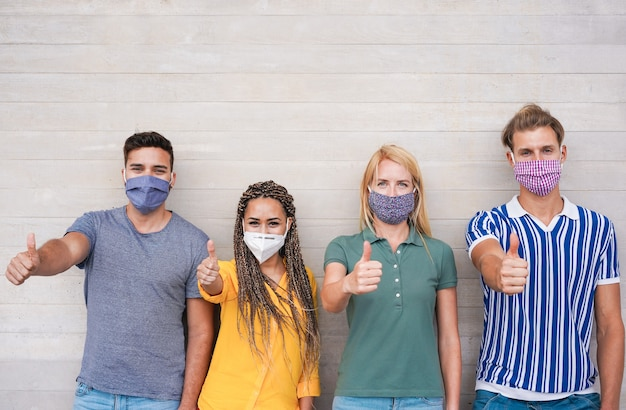 Young people with thumbs up wearing face protective masks for coronavirus prevention