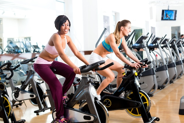 Young people - women spinning in the gym on fitness bicycles