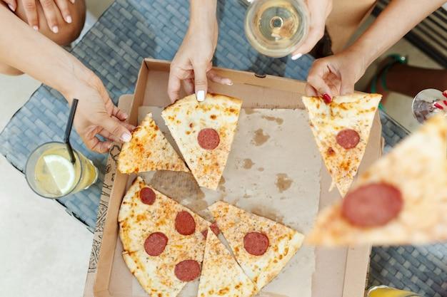 段ボール箱の上面図から熱いおいしいピザのスライスを取る若者の女性
