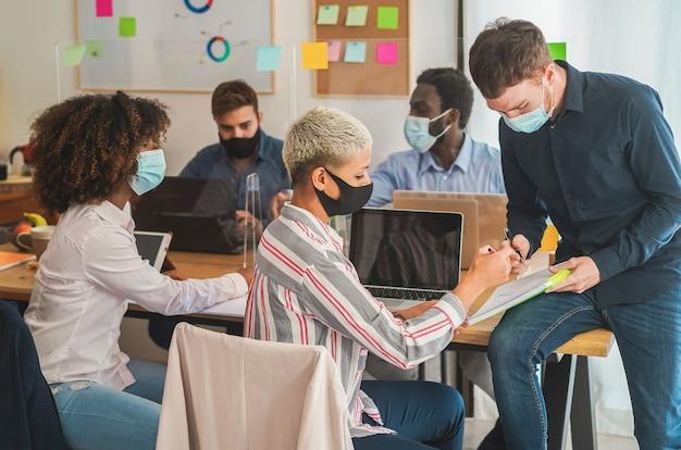 コロナウイルスの拡散防止のための保護マスクを着用しながらコワーキングオフィス内で働く若者