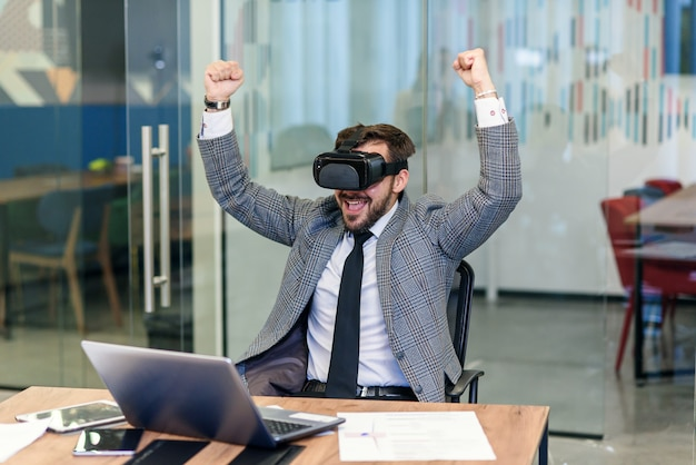 Young people working in the office, creative bearded man trying a new product or playing game with virtual reality goggles