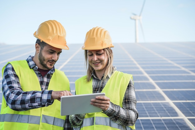신 재생 에너지 농장에서 디지털 태블릿으로 작업하는 젊은 사람들-얼굴에 초점