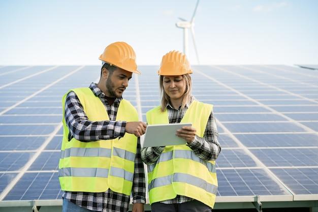 신 재생 에너지 농장에서 디지털 태블릿을 사용하는 젊은 사람들