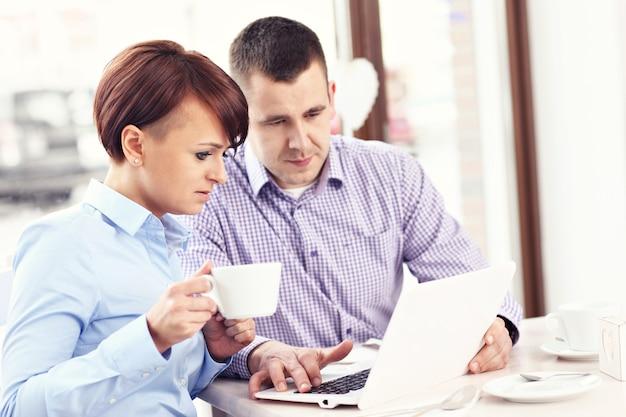 Молодые люди работают с ноутбуком в ресторане