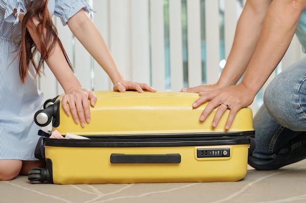 Молодые люди застегивают чемодан