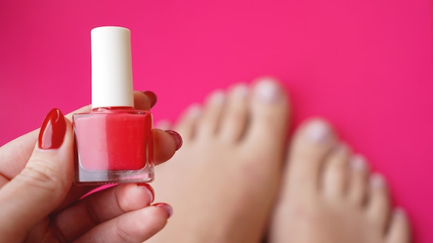Молодые идеальные ухоженные женские ноги на розовом фоне. заботьтесь о ногтях и чистой, мягкой, гладкой коже тела. салон красоты педикюра и маникюра