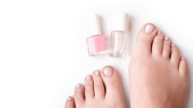Ноги молодой идеальной ухоженной женщины на белом фоне. заботьтесь о ногтях и чистой, мягкой, гладкой коже тела. салон красоты педикюра и маникюра