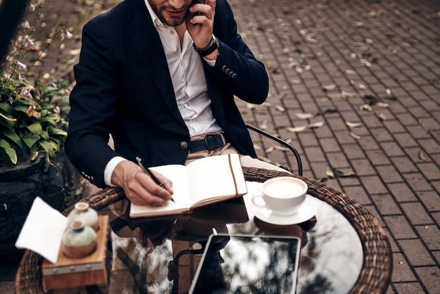 若い完璧主義者。彼のスマートフォンで話し、屋外のレストランに座っている間に何かを書き留めるスマートカジュアルな服装の若い男の上面図をクローズアップ