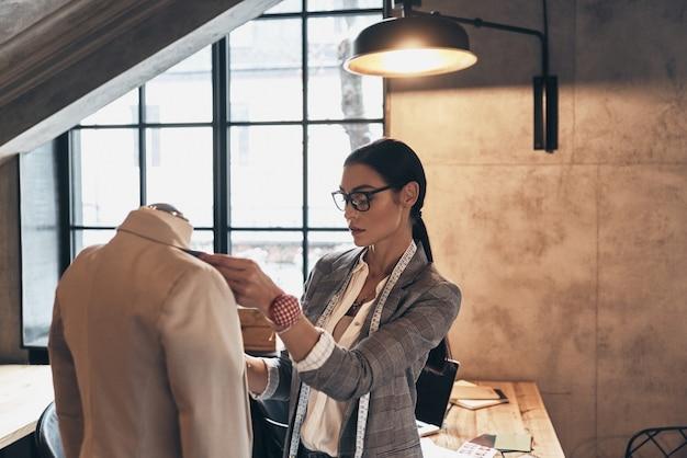 Юный перфекционист. серьезная молодая женщина в очках регулирует воротник куртки на манекене, стоя в своей мастерской