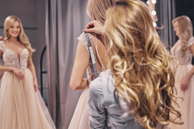 若い完璧主義者。試着室に立っている間花嫁を測定する若い女性
