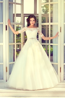 Молодая, идеально выглядящая невеста одета в шикарное традиционное свадебное платье.