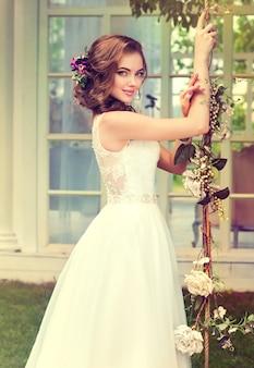 Молодая, идеально выглядящая невеста одета в шикарное свадебное платье.